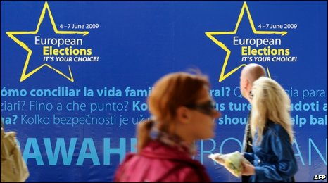 People pass an EU election poster in Brussels, May 2009