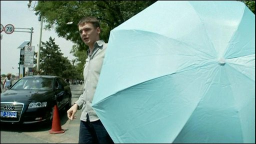 The BBC's James Reynolds is blocked by an umbrella