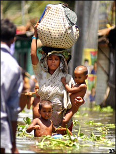 A Bangladeshi flood victim wades through flooded streets with her children