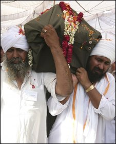 Sikhs carry the coffin containing the body of Sant Ramanand in Jalandhar in the northern Indian state of Punjab, Thursday, June 4, 2009