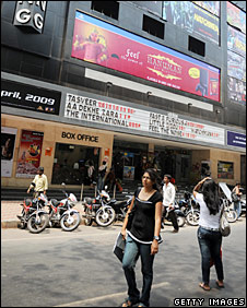 Pedestrians walks in front of a multiplex cinema in Mumbai on April 4, 2009