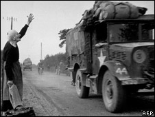 A French woman hails an Allied vehicle in Normandy, 1944