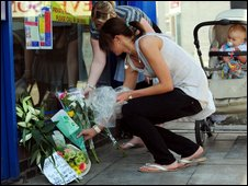 People leave floral tributes at the scene