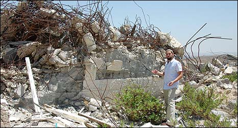 Yehoyada Nizri, resident of Amona outpost, next to remains of houses destroyed in 2006