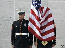 US troops stand to attention beside the US flag