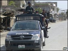 Police officers patrol a road during a curfew in Bannu  - 9 june