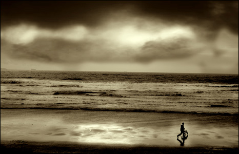 A man walks his dog along Newgale Beach in Pembrokeshire on a stormy day (Karen Lewis).