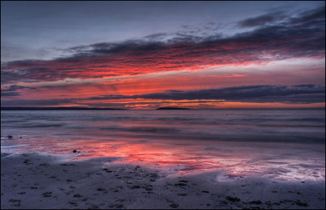 Evening colours fill the skies over Penmaenmawr beach, the Menai Strait and Puffin Island (Kris Williams).