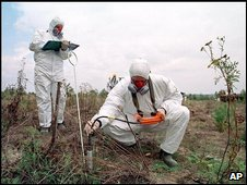 File photo from 1999 of two men checking pollution levels in the soil near Chernobyl
