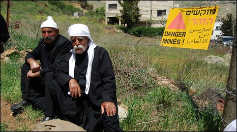 Two Syrian Druze men sitting near a minefield