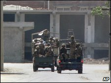 Paramilitary troops patrol on a road during the curfew in Bannu