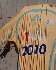 "On 10 June 2009 Workers hang a giant soccer shirt that reads ""one year to go"" to the 2010 World Cup to be held in South Africa in Cape Town, South Africa"