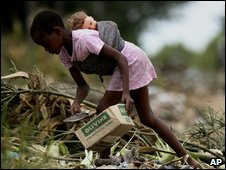A young girl goes through a rubbish tip while carrying a doll (file photograph)