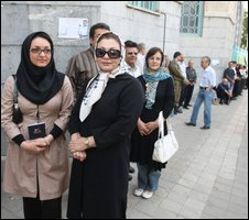 Iranians wait outside a polling station in Tehran