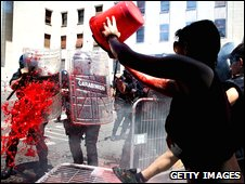 Protesters throws bucket of red liquid at police