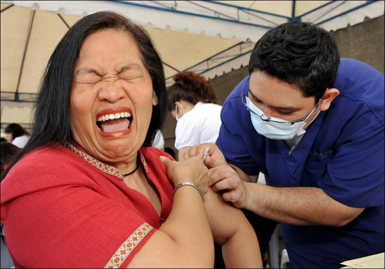 Woman in pain in Manila, the Philippines, as she receives flu jab