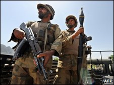 Pakistani army troops stand alert on a vehicle as they patrol in the village of Pir Baba in troubled Buner district on May 22, 2009