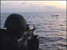 Swedish Armed Forces soldier aims machine gun at a boat with suspected pirates in the Gulf of Aden on 26 May 2009