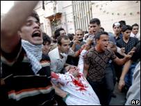 متظاهرون يحملون جثة قتيل في طهران