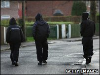 Three boys in hooded tops walk along street