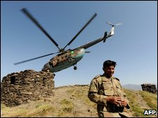 Pakistani army officer walks down from a hill top after army landing in a helicopter dropping foreign media representatives in Mingora on June 3, 2009