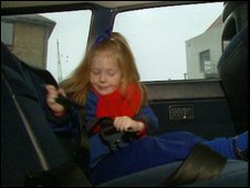 Child putting on her seat-belt