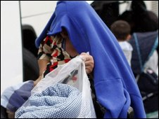 A Romanian woman covers her head as she arrives at a Belfast leisure centre