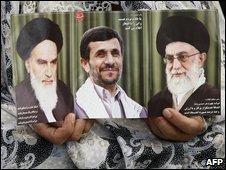 An Iranian woman holds portraits of Ayatollah Khomeini (L), Iranian President Mahmoud Ahmadinejad (C) and Ayatollah Khamenei (R)