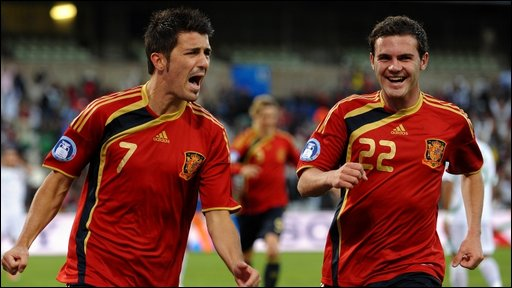 David Villa celebrates his goal against Iraq with Juan Manuel Mata