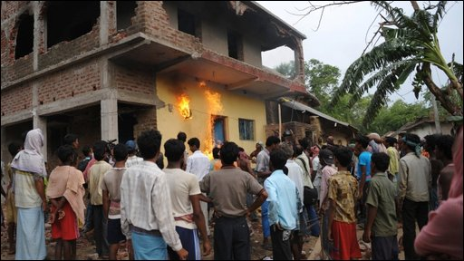 Indian villagers watching as Communist Party worker's house set alight