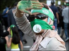 An Iranian opposition supporter wearing a mask at a protest in Tehran