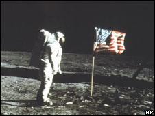 Astronaut Buzz Aldrin stands on the Moon next to an American flag