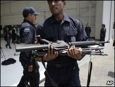 A federal police officer carries weapons seized in Mexico City on 17 June