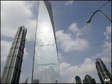 Shanghai skyline (left - copyright AP) and people walking past a homeless person (right)