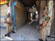 Pakistani troops stand guard on a street in Mingora, the main town in Swat valley, Pakistan on Wednesday June 3, 2009