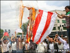Iranian pro-government supporters burn a US flag in Tehran