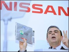 Nissan boss Carlos Ghosn holds up a battery unit
