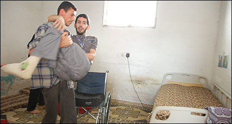 Yahya Abu Saif is carried to his bed at home by his brother