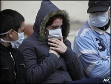 People in Buenos Aires wear masks as they wait for treatment on 18 June