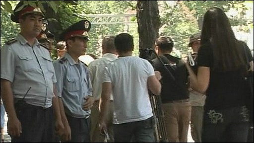 Police officers flank protesters in Almaty