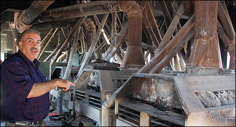 Mahmoud Hamada, manager of al-Badr flour mill, amid destroyed machinery