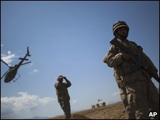 An army helicopter flies over Pakistani soldiers in a military base on top of a hill in Chupria, in the upper Swat Valley, Pakistan, Saturday, June 20, 2009