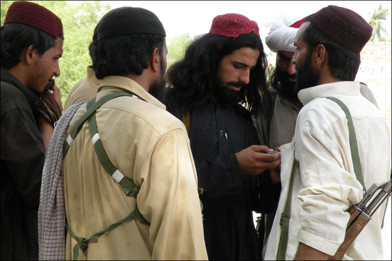 A group of Taliban look at a mobile phone