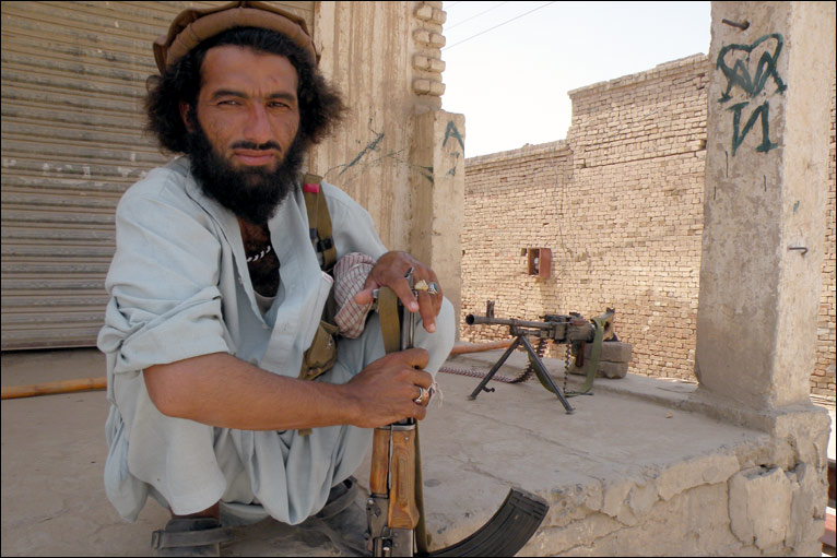 The squatting Taliban guard in the picture is manning a post on a street corner just outside the offices of an anti-Baitullah Taliban group led by Haji Turkistan Bhittani.