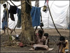 A Tamil woman sits with her children while getting their clothes dry next to their tent at the Manik Farm refugee camp located on the outskirts of the northern Sri Lankan town of Vavuniya Tuesday, May 26, 2009.