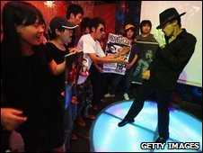 A Michael Jackson impersonator dances at a bar in Beijing, China