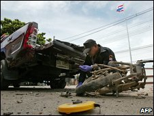 A Thai officer inspects the site of an explosion which killed two policemen in Pattani on June 16, 2009