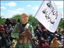 An al-Shabab fighter stands guard over a crowd during a court session in Mogadishu on 22 June 2009