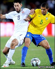 Brazil's Felipe Melo tussels with Fulham's Clint Dempsey in the Confederations Cup final