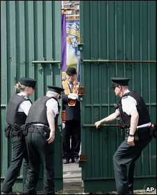 Police open the security gates at Workman Avenue for an Orange Order parade